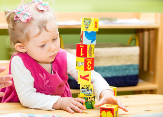 Little child girl playing with toy letter and number blocks