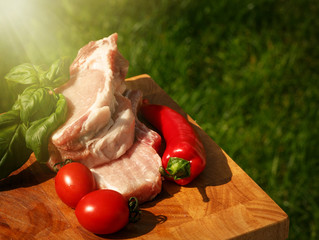 Raw pork steaks on wooden table with tomatoes, peppers and basil