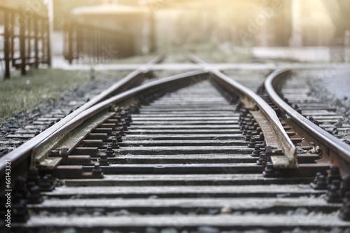 Leinwandbild Motiv Bahngleis in der Abendsonne mit Haltestelle