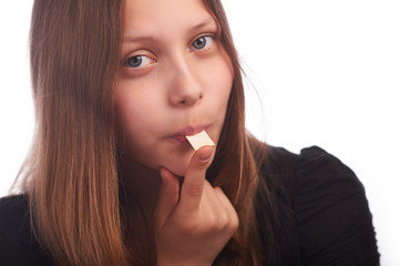 teen girl eating bubblegum on white background