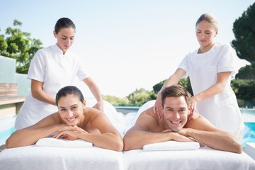 Smiling couple enjoying couples massage poolside