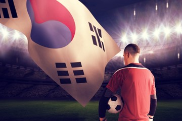Composite image of goalkeeper in red holding the ball