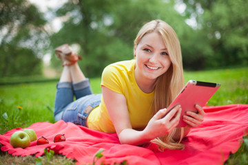 girl lying in the park with tablet