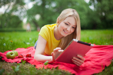 blonde girl lying in the park with tablet