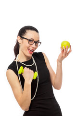 brunette businesswoman in black dress holding apple and dumbbell