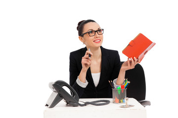 businesswoman sitting in office chair and writing in notebook