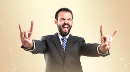 Young businessman doing the horn sign over ocher background