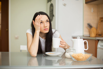 girl having breakfast in the kitchen with headache