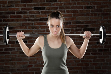 Sweat fit woman lifting dumbbells on brick background
