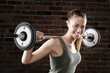 Smiling Sweat beautiful girl lifting dumbbells