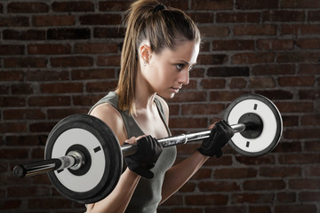 PSweat beautiful girl lifting dumbbells on dark background