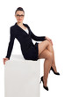 brunette woman in black skirt and jacket sitting on cube