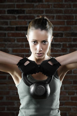 Young fit woman lifting kettle bell and looking at camera