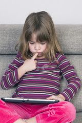 Little girl playing with a digital tablet