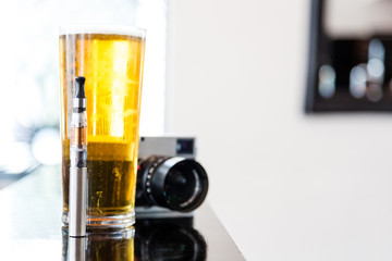 Pint of beer with an e-cigarette and camera