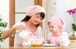 Mother and child preparing cookies together at kitchen
