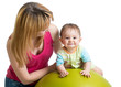mother doing gymnastics to baby on fitness ball
