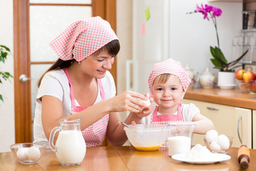 Young woman and her daughter cooking together at home