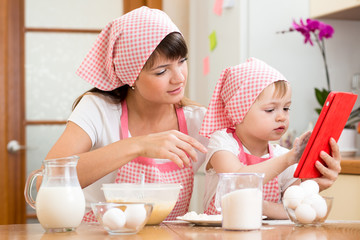 Mother and child preparing pastry together at kitchen and lookin