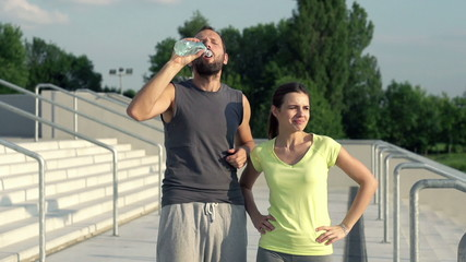 Joggers couple drinking water after run, super slow motion