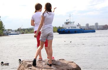 Девочка показывает рукой в сторону корабля