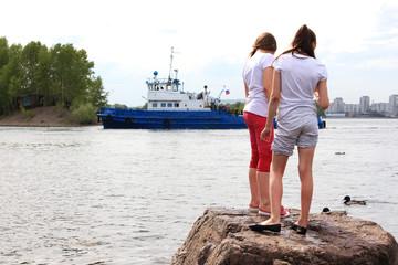 Две девочки на набережной Енисея с плывущим кораблём