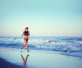 Athletic girl runs along the sea, evening jog on the beach