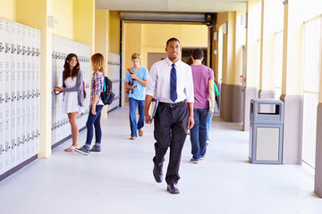 High School Students And Teacher Walking Along Hallway