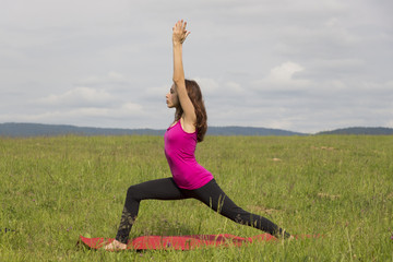 Woman doing Warrior I pose outdoors during yoga