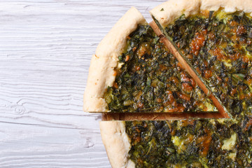 useful pie with spinach, cheese on wooden table close-up