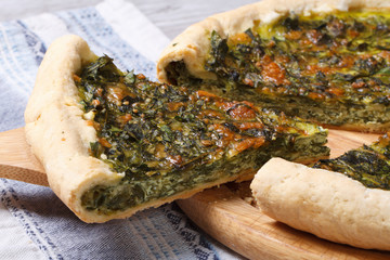 Piece of pie with green stuffed spinach, eggs and cheese