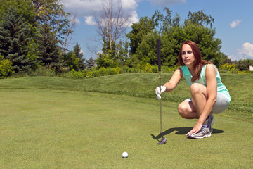 Woman lining up her putt on the golf green