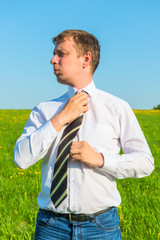 manager adjusts his tie in a green field