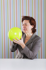 Businesswoman blowing a balloon