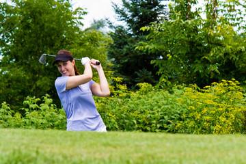 Woman golfer swining her club on the fairway