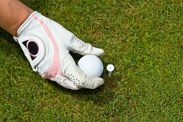 Close-up of a gloved hand of a woman golfer placing golf ball on