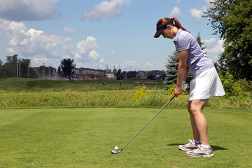 Female golfer prepares to tee off