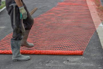 Builder worker unrolling orange safety fence