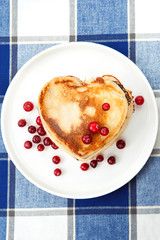 Love heart pancakes with cranberries on porcelain plate. Closeup
