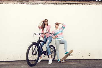 Two friends standing together with skateboard and bicycle.