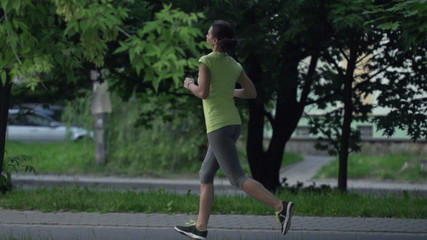 Young woman jogging in the city park, super slow motion
