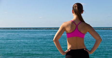 Woman in sports bra looking at the ocean