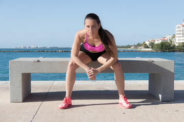 Determined, fit hispanic woman sitting on a bench