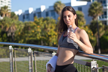 Hispanic woman drinking water during a workout session