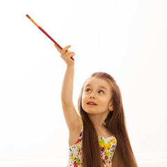Little girl with a paintbrush on white background