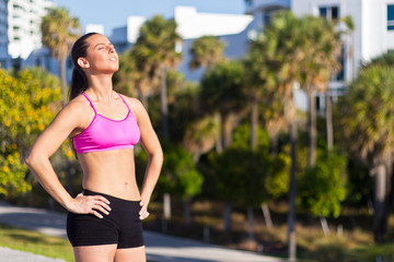 Hispanic woman in fitness attire basking in the sun