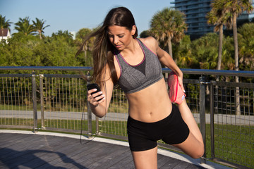 Hispanic girl stretches and listens to music during a fitness se