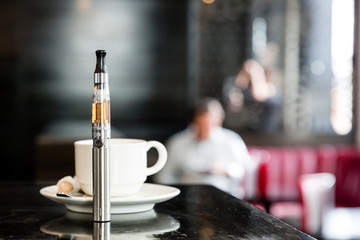 E-cigarette on a bar counter with a cup of coffee
