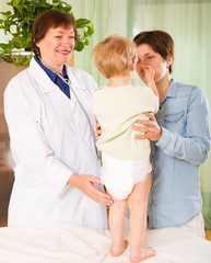 mature  pediatrician doctor examining toddler
