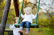 Two little sisters having fun on a swing